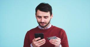 Hombre de Serios hacer una transacción en línea usando su smartphone y una tarjeta de crédito en un estudio con una pared azul de almacen de video