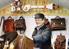 Hombre de Smilling que ofrece bolsos de cuero hechos a mano en el mercado de la Navidad de Vilna Foto de archivo libre de regalías