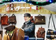 Hombre de Smilling que vende bolsos de cuero hechos a mano en el mercado de la Navidad de Vilna Fotografía de archivo libre de regalías