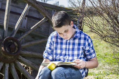 Hombre de Student.Young que lee un libro en al aire libre con la manzana amarilla. Fotografía de archivo