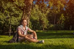 Hombre de universidad hermoso que lee un libro y que bebe el café en parque del campus Estudiante serio del individuo que aprende Fotografía de archivo libre de regalías