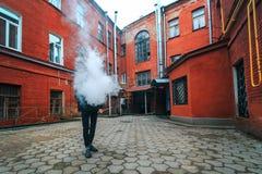 Hombre de Vape Un individuo blanco joven hermoso en vidrios sopla el vapor de un cigarrillo electrónico en una vieja yarda roja d Imagenes de archivo