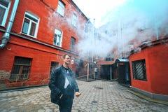 Hombre de Vape Un individuo blanco joven hermoso en vidrios sopla el vapor de un cigarrillo electrónico en una vieja yarda roja d Imagen de archivo