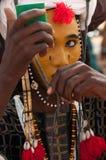 Hombre de Wodaabe que comprueba el maquillaje en un espejo, Gerewol, Niger Imagen de archivo libre de regalías