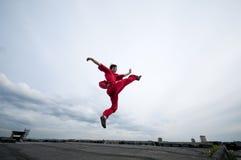 Hombre de Wushoo en arte marcial de la práctica roja Fotografía de archivo
