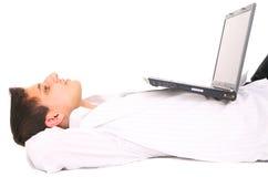 Hombre de Youmg que se reclina con la computadora portátil Fotos de archivo