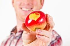Hombre de Youn con un Apple con los corazones Imágenes de archivo libres de regalías