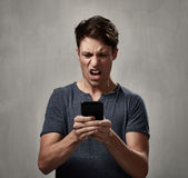 Hombre decepcionado con el teléfono celular Imagen de archivo libre de regalías