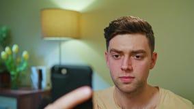Hombre decepcionado que bebe y que usa el teléfono móvil foto de archivo