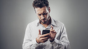 Hombre decepcionado que mecanografía con su smartphone Imagen de archivo