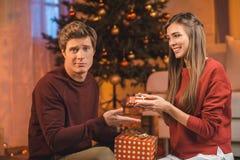 hombre decepcionado que mira la cámara mientras que intercambia los regalos de la Navidad por la novia imagen de archivo libre de regalías