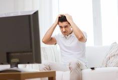 Hombre decepcionado que ve la TV en casa Foto de archivo libre de regalías