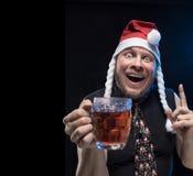 Hombre del actor cómico en casquillo con las trenzas con un vidrio de cerveza, antes de la Navidad y el Año Nuevo Imagen de archivo libre de regalías