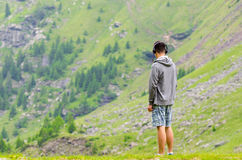 Hombre del adolescente con los auriculares que mira las montañas melacholic Foto de archivo