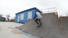 Hombre del adolescente que anda en monopatín en deporte extremo del skatepark en la cámara lenta 4K Adquirido el negro de Gopro 6 almacen de metraje de vídeo