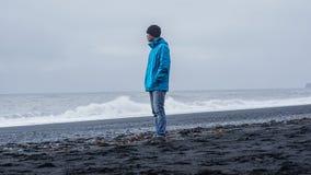 Hombre del advanture de Asina en la playa del negro de Islandia con el espacio de la copia Imagenes de archivo