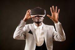 Hombre del Afro en el traje blanco que realiza la simulación de la realidad virtual Imagen de archivo libre de regalías