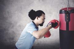 Hombre del Afro que perfora un saco del boxeo Imagen de archivo libre de regalías