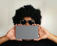 Hombre del Afro que sostiene la tarjeta en blanco Fotos de archivo libres de regalías