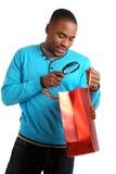 Hombre del afroamericano con magnificar del bolso de compras Imagen de archivo