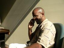 Hombre del afroamericano en el teléfono celular en las sombras Fotografía de archivo