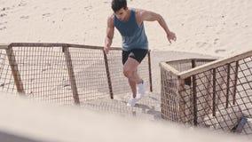 Hombre del ajuste que funciona con para arriba los pasos en la playa almacen de metraje de vídeo