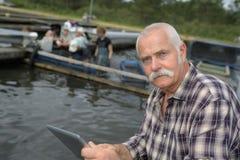 Hombre del alto directivo que trabaja en granja de pescados fotos de archivo