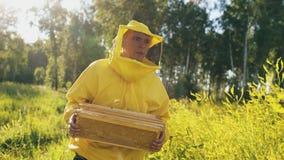 Hombre del apicultor con el marco de madera que camina en campo del flor mientras que trabaja en colmenar Fotos de archivo libres de regalías