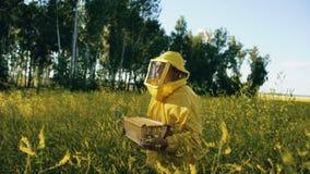 Hombre del apicultor con el marco de madera que camina en campo del flor mientras que trabaja en colmenar Foto de archivo