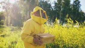 Hombre del apicultor con el marco de madera que camina en campo del flor mientras que trabaja en colmenar Foto de archivo libre de regalías