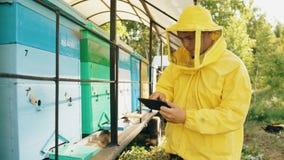 Hombre del apicultor con la tableta que comprueba colmenas de madera antes de cosechar la miel en colmenar Fotografía de archivo libre de regalías
