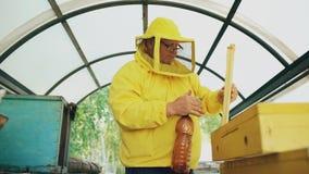 Hombre del apicultor que riega el marco de madera con el rociador y la disposición en colmena en colmenar Imágenes de archivo libres de regalías