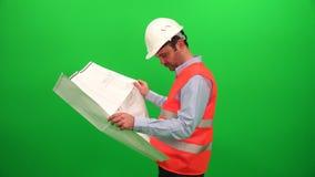 Hombre del arquitecto que analiza plan del proyecto del esquema metrajes