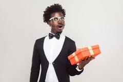 Hombre del asombro que sostiene la caja de regalo y chocado foto de archivo