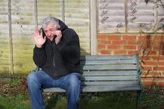 Hombre del ataque de pánico en un banco Fotos de archivo