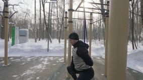 Hombre del atleta que hace ejercicio agazapado con el ampliador del deporte en la tierra de deportes de invierno almacen de video
