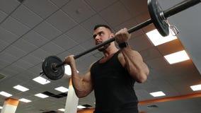 Hombre del Barbell en el levantamiento de pesas de la aptitud del bíceps del entrenamiento del gimnasio