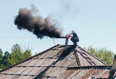 Hombre del barrido de chimenea en chimenea de la limpieza del uniforme del trabajo en el tejado Fotografía de archivo