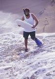 Hombre del bicho raro con la tarjeta de la boogie en la playa Foto de archivo libre de regalías