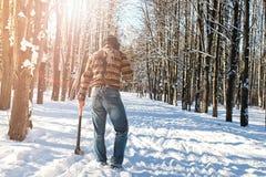 Hombre del bosque del invierno del abedul con el hacha Foto de archivo libre de regalías