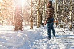Hombre del bosque del invierno del abedul con el hacha Foto de archivo