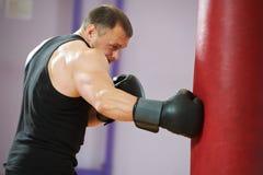 Hombre del boxeador en el entrenamiento del boxeo con el bolso pesado Foto de archivo libre de regalías