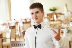 Hombre del camarero con la bandeja en el restaurante Imagen de archivo libre de regalías