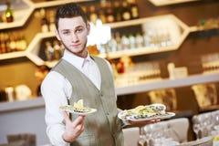 Hombre del camarero en restaurante abastecimiento Imágenes de archivo libres de regalías