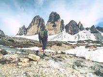 Hombre del caminante con la corriente de la travesía de la mochila en piedras en Dolomiti imagen de archivo libre de regalías