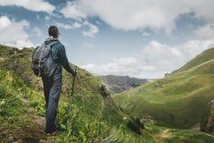 Hombre del caminante con la mochila y postes el emigrar que descansan y que miran las montañas en el verano al aire libre, vista  foto de archivo libre de regalías