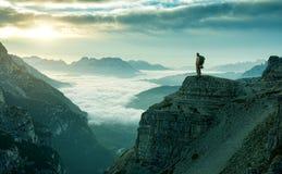 Hombre del caminante que se coloca en el borde de la roca Foto de archivo libre de regalías