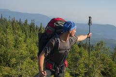 Hombre del caminante que se coloca en el top de la montaña en día soleado y las demostraciones en Foto de archivo libre de regalías