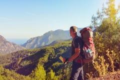 Hombre del caminante que se coloca en montañas y que mira en la distancia Imagen de archivo libre de regalías
