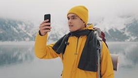 Hombre del caminante usando el smartphone que toma una foto de la naturaleza del invierno El turista admira la naturaleza y hace  metrajes